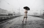 Vrouw in de regen op treinstation