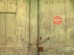 Old wooden door in France with sign Sortie Vehicules Ne Pas Stationer Merci