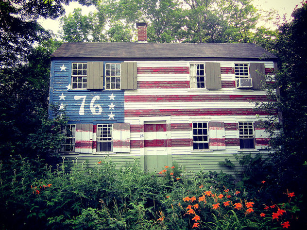 Old wooden house in the USA with American flag painting